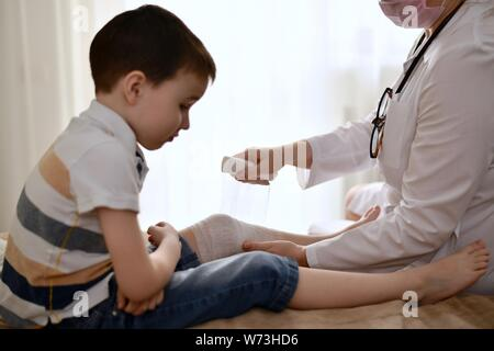 The doctor bandages the sick knee of a child with a bandage. Baby sits upset on the bed, folding his arms and head down. - Stock Photo