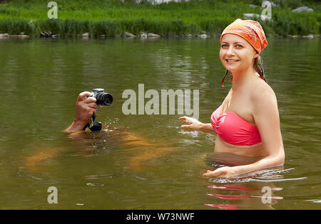 Young beautiful wet woman in swimsuit is standing in river while man is taking photos with digital camera from the surface of the water, eco-tourism. - Stock Photo