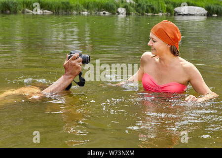 Young pretty wet woman in swimsuit is swimming in river and white man is photographing her by waterproof digital camera. - Stock Photo