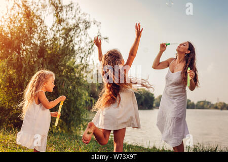 Mother helps daughters to blow bubbles in summer park. Kids having fun playing and catching bubbles outdoors. Family spending time together - Stock Photo