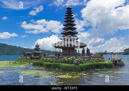 Pura Ulun Danu Bratan, Bali. Hindu temple surrounded by flowers on Bratan lake, Bali. Water temple with blue sky in the background. - Stock Photo