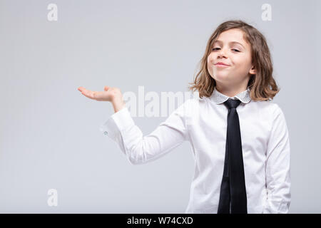 Cute little schoolgirl in uniform extending her empty palm to the side over a white background with copy space for product placement or advertising - Stock Photo