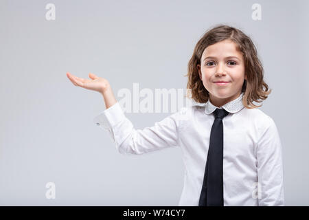 Young girl in school uniform holding out her empty palm to the side with a smile in a concept of product placement and advertising over a white backgr - Stock Photo