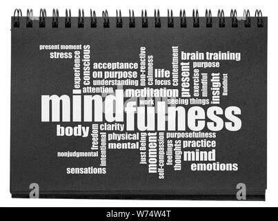 mindfulness word cloud - white text in an isolated black paper sketchbook - Stock Photo