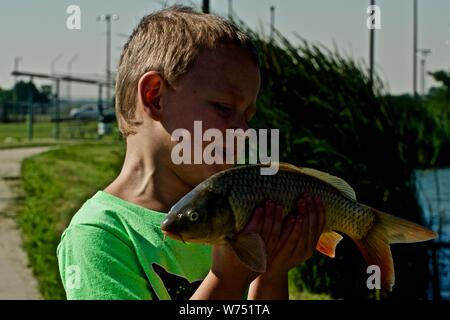 My Grandson, Connor with his First Fish, River Carp, Lindsey Park Public Fishing Lake, Canyon, Texas. - Stock Photo