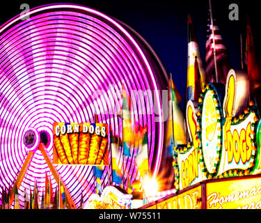 A spinning ferris wheel with changing colors is the centerpiece of the midway at a county fair. - Stock Photo