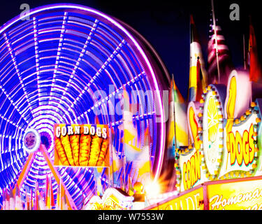 A spinning ferris wheel dominates the midway at a county fair in North Florida. - Stock Photo