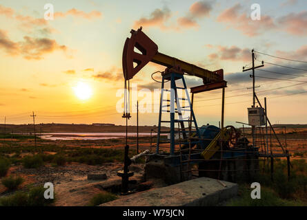 Oil rig pump against a colorful sunset sky
