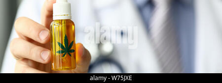 Male doctor hold bottle with marijuana oil - Stock Photo