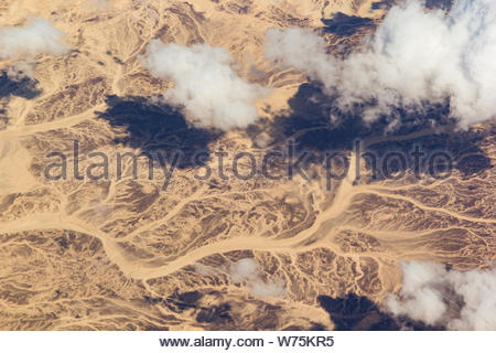 Clouds over a desert landscape. View from the airplane window. - Stock Photo