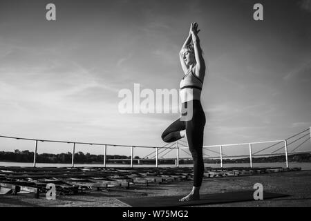 Woman practicing yoga on sunny day. Vriksasana, Tree pose - Stock Photo