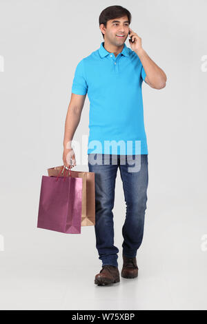 Man carrying shopping bags and talking on mobile phone - Stock Photo