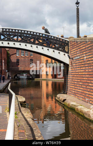 A man leans forward as he crosses the Bar Lock Bridge at Gas Street Basin, Birmingham. In the distance is the Broad Street Tunnel, UK - Stock Photo