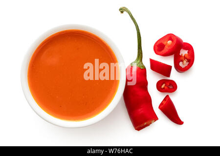 Peri peri chilli sauce in a white ceramic bowl next to a cut up chilli pepper isolated on white from above. - Stock Photo