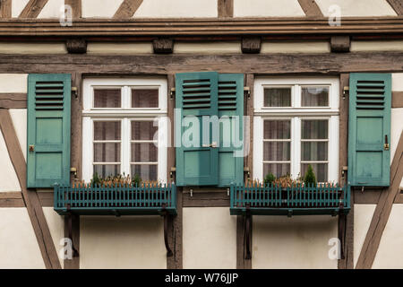 Sindelfingen, Baden Wurttemberg/Germany - May 11, 2019: Two colorful wooden windows on a traditional half-timbered house facades. - Stock Photo