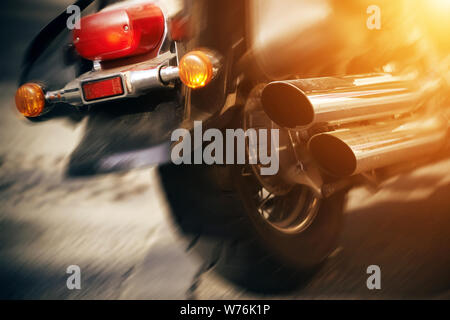 A beautiful cool motorcycle with red headlights and a silver pipe rides quickly on an asphalt road, illuminated by bright light. - Stock Photo