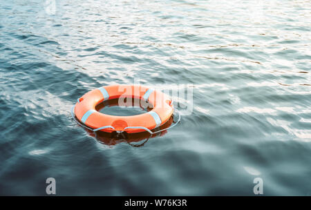 Life buoy floating on the water with copy space - Stock Photo