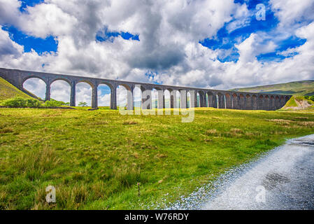View of a large old Victorian railway viaduct across valley in rural countryside scenery panorama - Stock Photo