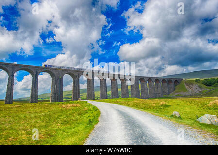 View of a large old Victorian railway viaduct across valley in rural countryside scenery panorama with train - Stock Photo