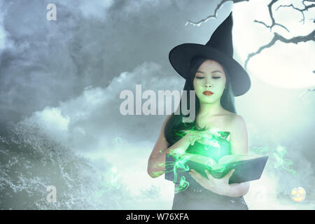 Asian witch woman in hat learns the spell from the magic book with moonlight background. Halloween concept - Stock Photo