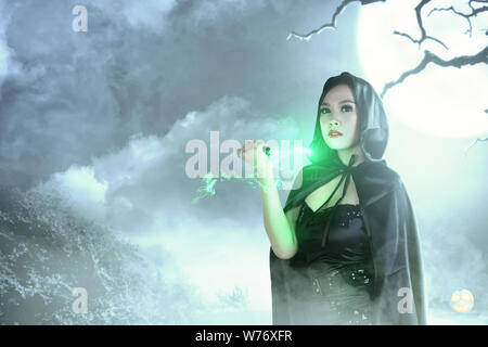Asian witch woman in black hooded doing ritual magic with a knife with moonlight background. Halloween concept - Stock Photo