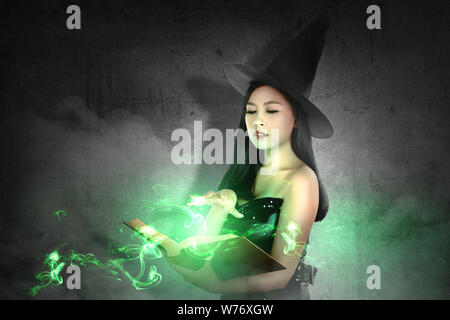 Asian witch woman in hat learns the spell from the magic book with a black wall background. Halloween concept - Stock Photo