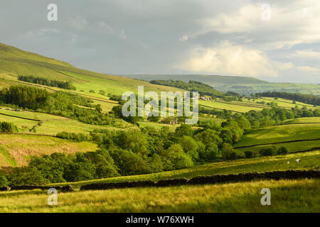 Long-distance picturesque evening view to Wharfedale (rolling clouds & hills, green pasture, sunlit valley) - Beamsley, Yorkshire Dales, England, UK.
