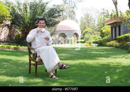 South Indian man having a cup of tea in a lawn - Stock Photo