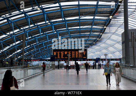 Travellers walk through Waterloo train station in London, UK. - Stock Photo