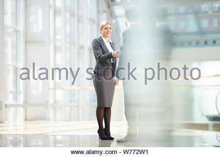 Smiling pretty young business lady in gray suit making handshake with business partner in lobby - Stock Photo