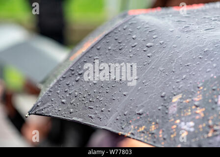 Raining Day, Heavy Rain in City, Drops on Surface of black Umbrella, People with Umbrellas during Storm - Stock Photo