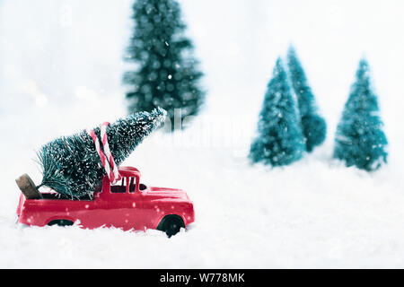A 1950's antique vintage red toy truck hauling a Christmas tree home through a snowy winter wonder land. Selective focus on vehicle with blurred backg - Stock Photo