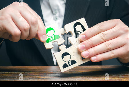 A businessman collects puzzles symbolizing a team of employees. The appointment of the head. Dismissal employee. The concept of the organization of th - Stock Photo