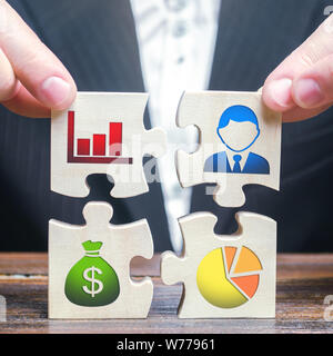 A businessman collects puzzles symbolizing individual elements and attributes of doing business. Project management. Good planning, Organization of th - Stock Photo