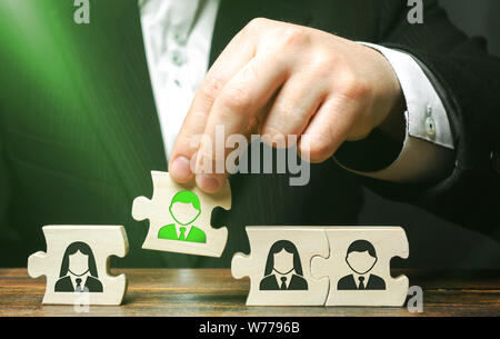 A businessman collects puzzles symbolizing a team of employees. The concept of creating a business team to perform tasks. Toxic employee, weak link. M - Stock Photo