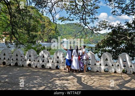 Kandy, Sri Lanka - July 6, 2016:  Framed view of a group of women taking a selfie on Kandy Lake shore - Stock Photo