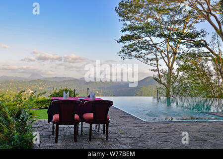 Kandy, Sri Lanka - July 7, 2016:  An outdoor dinning table near a pool overlooking a view on a vast landscape near Kandy, Sri Lanka - Stock Photo