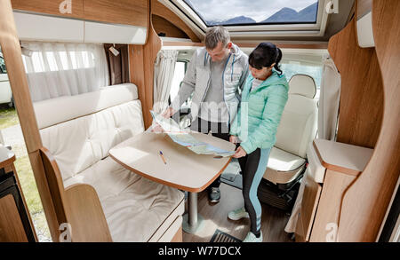 Couples in RV Camper looking at the local map for the trip. Family vacation travel, holiday trip in motorhome, Caravan car Vacation. - Stock Photo