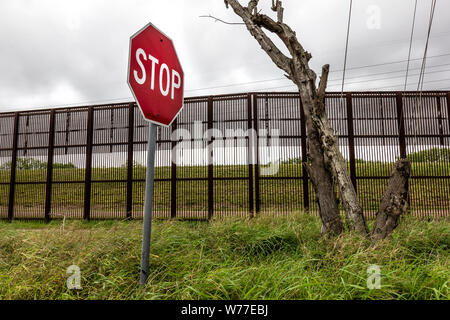 Stop sign in front of the Border wall with Mexico, Brownsville, Texas, USA - Stock Photo
