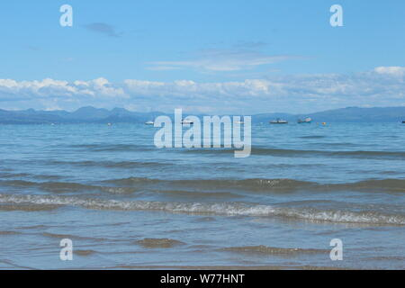 Image of the calm sea, with mountains and small clouds in the distance, on a sunny day in Abersoch - Stock Photo