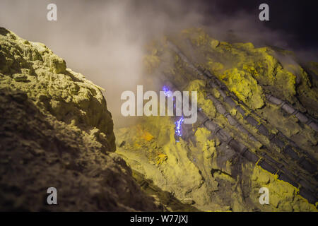 famous the Blue fire inside the crater of the Ijen volcano on Java Island, Indonesia, where miners collect sulfur that is coming from volcanic gasses - Stock Photo