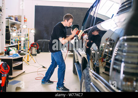 Polishing the car body at the service station.