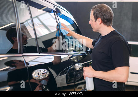 The man is wiping with a cloth body of a brilliant car - Stock Photo