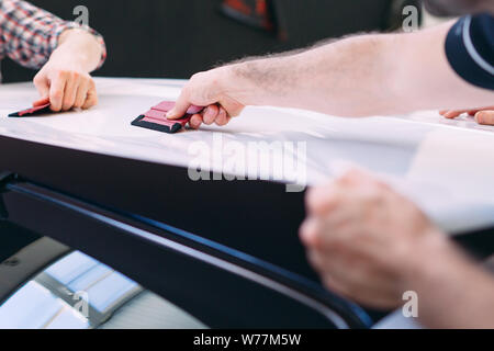 The man is wiping with a cloth body of a brilliant car. - Stock Photo