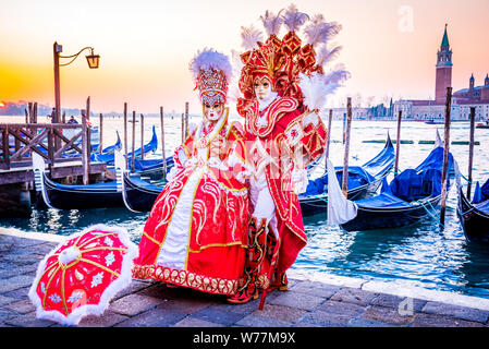 Carnival of Venice, beautiful mask at Piazza San Marco with gondolas and Grand Canal, Venezia, Italy. - Stock Photo