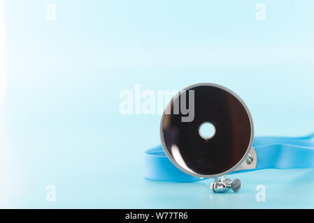 Ear professional instrument on blue background. - Stock Photo