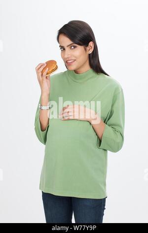Pregnant woman eating burger