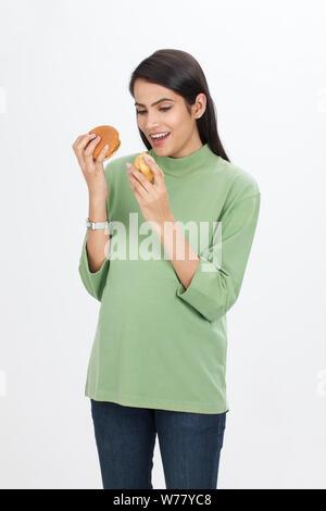 Pregnant woman eating burger and samosa