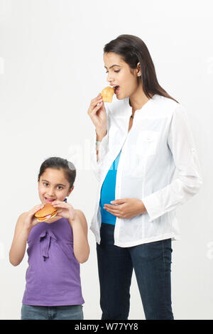Pregnant woman and her daughter eating fast food