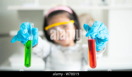 Happy asian kid with two glass tube when learning scientific in laboratory. - Stock Photo